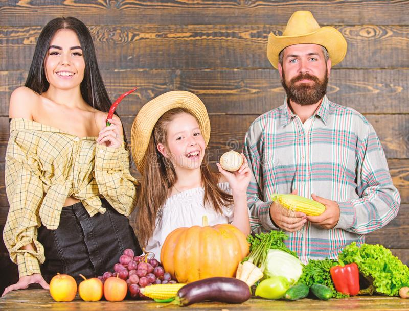 Farm market with fall harvest. Family farm festival concept. Man bearded rustic farmer with kid and wife. Family father. Farmer mother gardener with daughter stock image