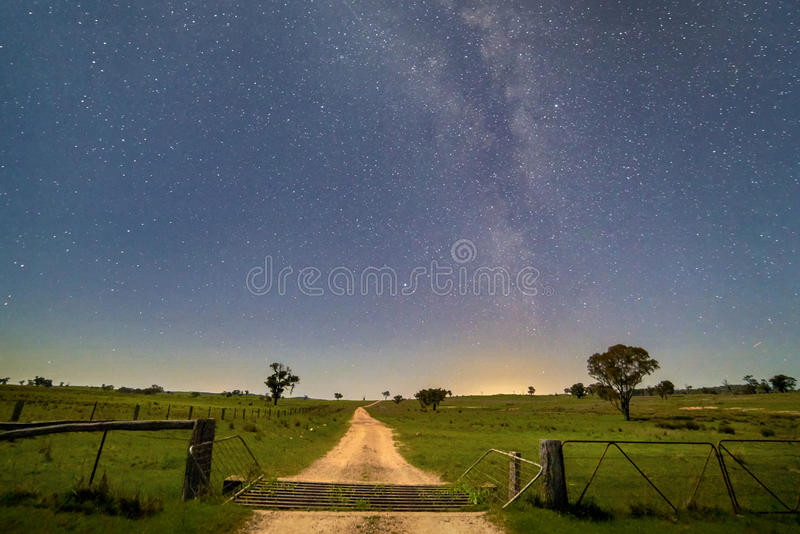 Farm road through a gate and fields at night under the milky way in mid western New South Wales, Australia stock images