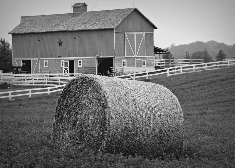 Farm Scene. In Lake Geneva, WI. with a round hay bale, white fence and a barn royalty free stock image