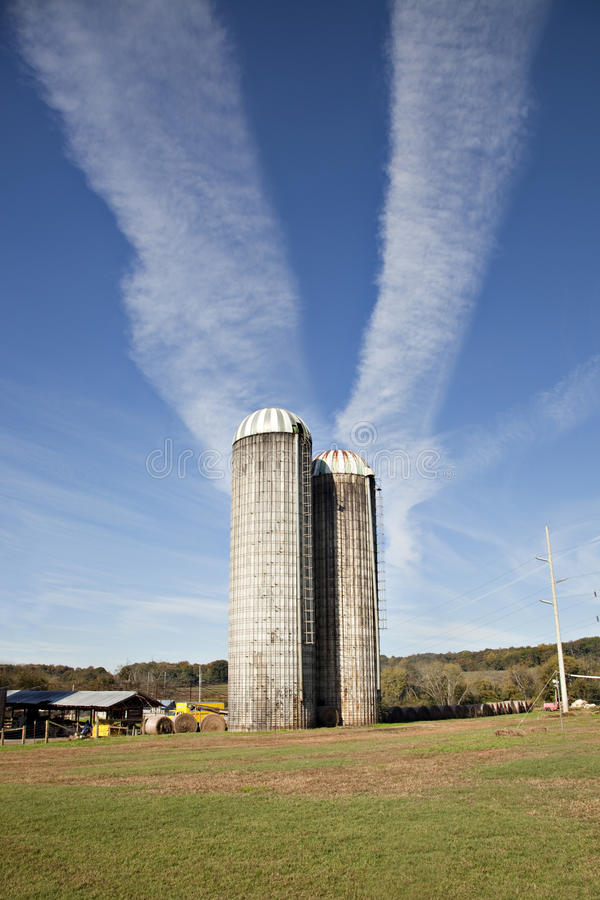Farm silos with jet contrails in sky