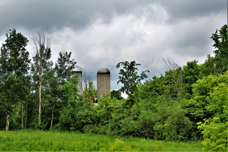 Farm silos located in Franklin County, upstate New York, United States. Rural farm and silos with surrounding green vegetation located in Franklin County royalty free stock image