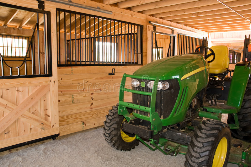 Farm tractor in barn royalty free stock photography