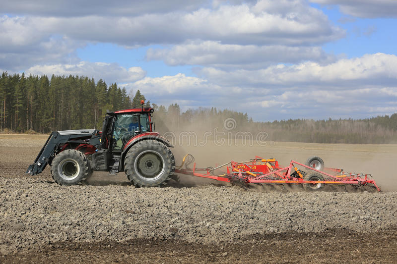 Farm Tractor and Cultivator on Spring Field stock photo
