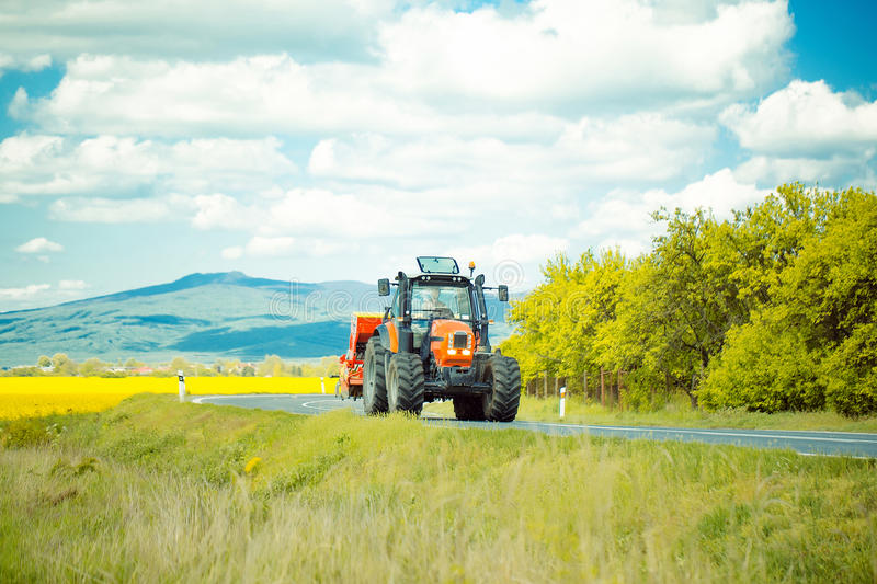 Farm tractor drives on road. Red farm tractor drives on road along beautiful field on summer sunny day on landscape background stock photography
