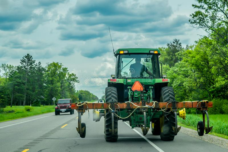 Farm Tractor Driving On Road royalty free stock photo