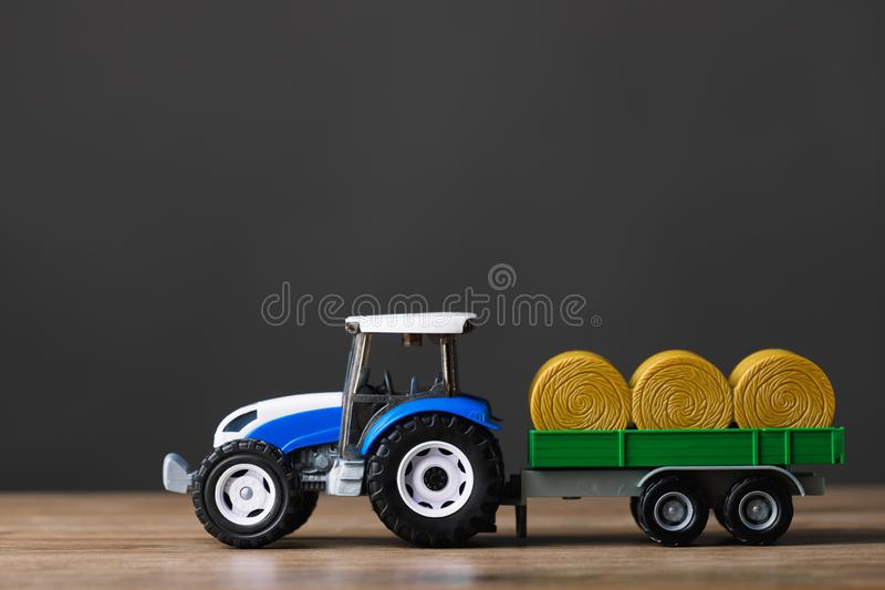 Farm tractor toy with hay trailer. Copy-space background royalty free stock images