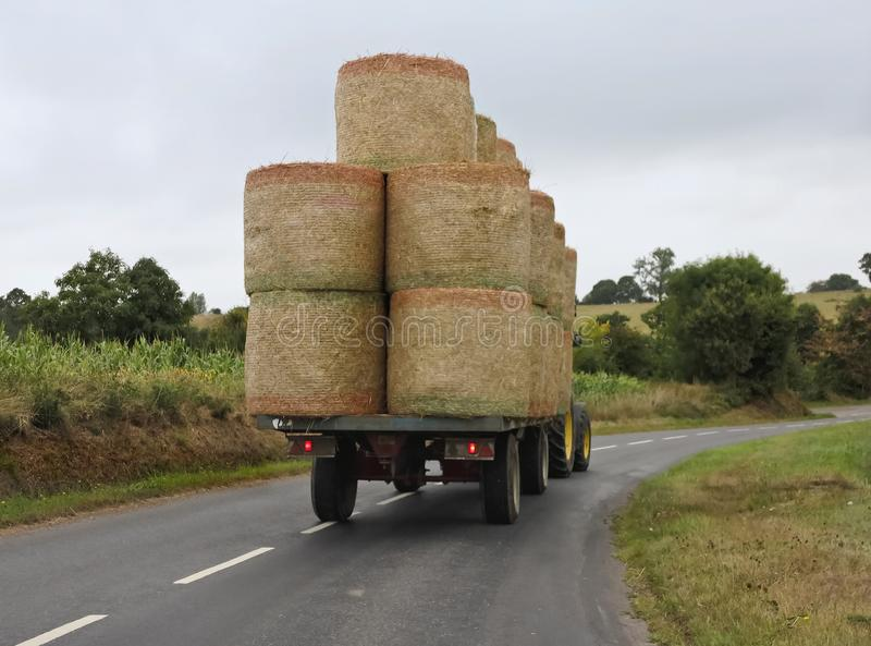 Farm tractor with trailer of hay bales. Farm tractor pulling trailer with hay bales stock images