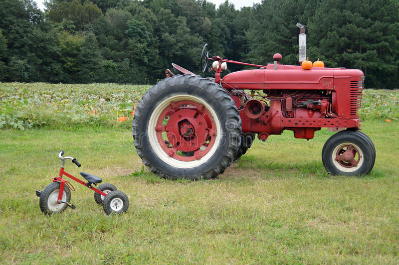 Farm tractor and tricycle. Large red farm tractor near a small tricycle in a farm field royalty free stock photo