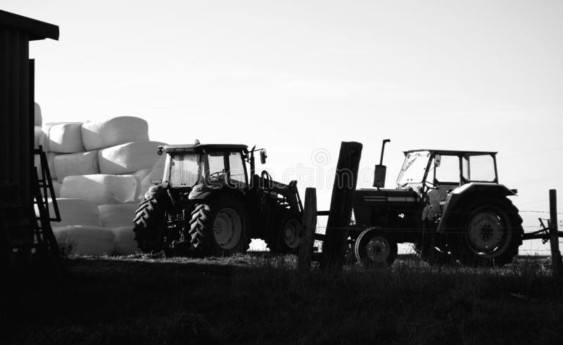 Farm Tractors Parked by Hay Bales. A classic artistic high contrast image of two tractors head to head a ford and a john deer old style cabin tractors parked by stock photos