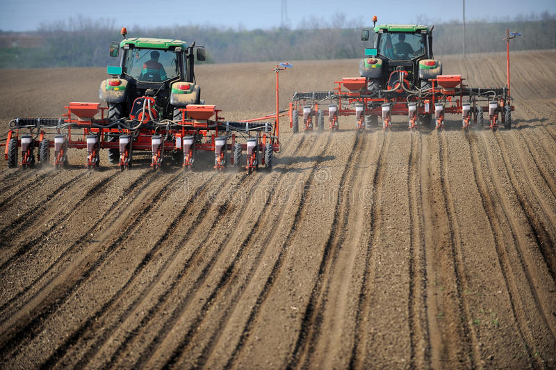 Farm tractors planting field. Two farm tractors planting a field in early spring stock images