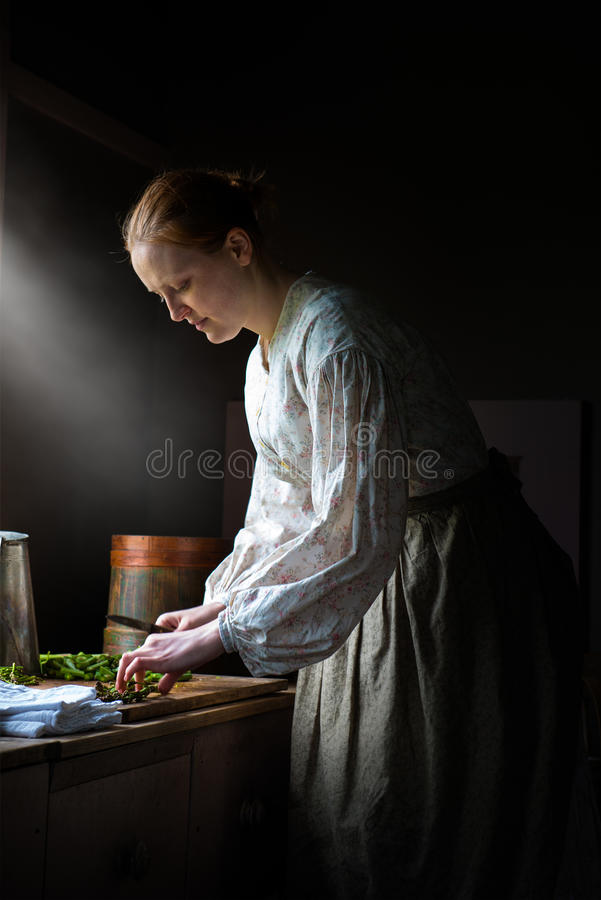 Farm Wife Cooking Dinner, Food. A housewife woman cooking dinner on the farm. The farmer wife is cutting asparagus while preparing dinner or supper for the