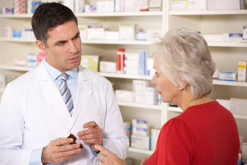 Farmacéutico americano con la mujer mayor en farmacia fotos de archivo