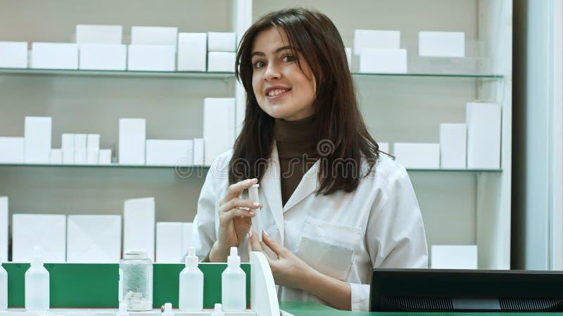 Farmacéutico amistoso con la botella de píldoras que habla con la cámara imágenes de archivo libres de regalías