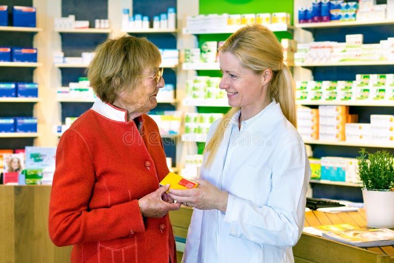 Farmacéutico amistoso que da la prescripción del cliente imagen de archivo libre de regalías