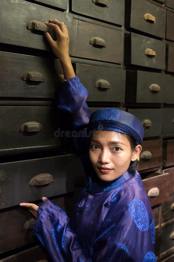 Farmacéutico asiático que trabaja en la farmacia oriental foto de archivo