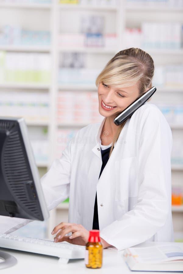 Farmacéutico atractivo sonriente que habla en el teléfono imagen de archivo