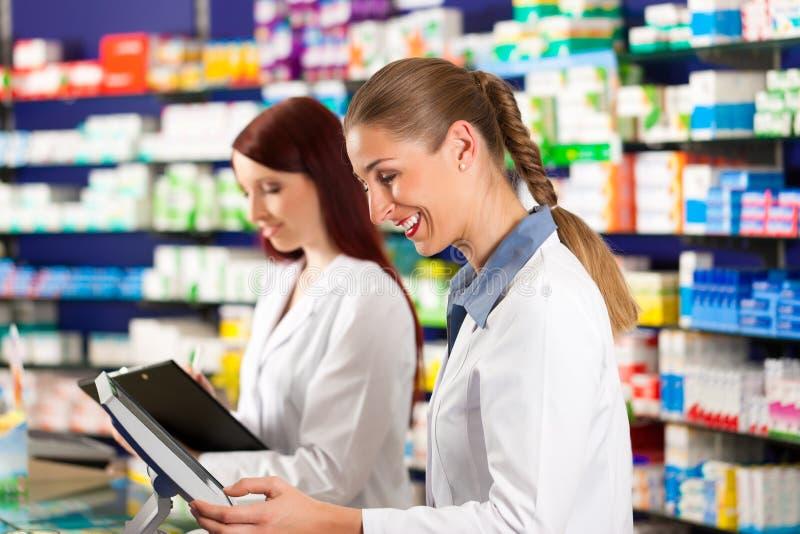 Farmacéutico con el ayudante en farmacia imágenes de archivo libres de regalías