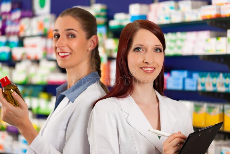 Farmacéutico con el ayudante en farmacia imagen de archivo