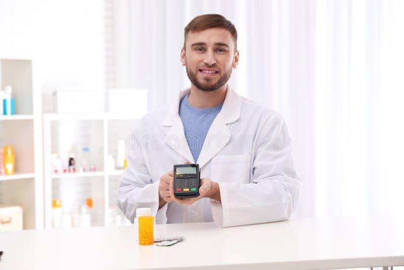 Farmacéutico con el terminal y las píldoras del pago fotografía de archivo libre de regalías