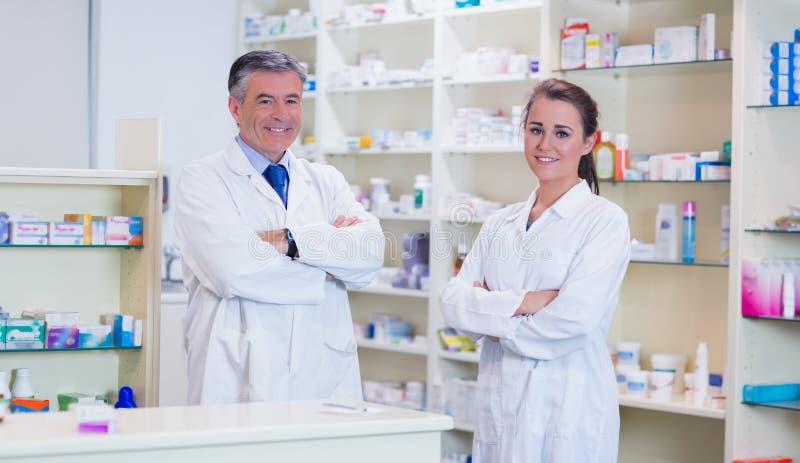 Farmacéutico con su aprendiz que se coloca con los brazos cruzados fotos de archivo