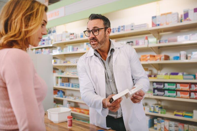 Farmacéutico con una caja de la medicina que da consejo al cliente foto de archivo libre de regalías