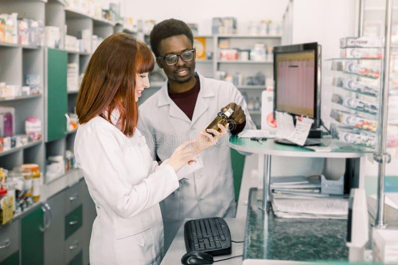 Farmacéutico de sexo femenino caucásico joven que habla con su colega africano del hombre sobre la nueva situación de la medicina imagenes de archivo