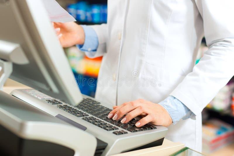 Farmacéutico de sexo femenino en el cajero en farmacia fotografía de archivo