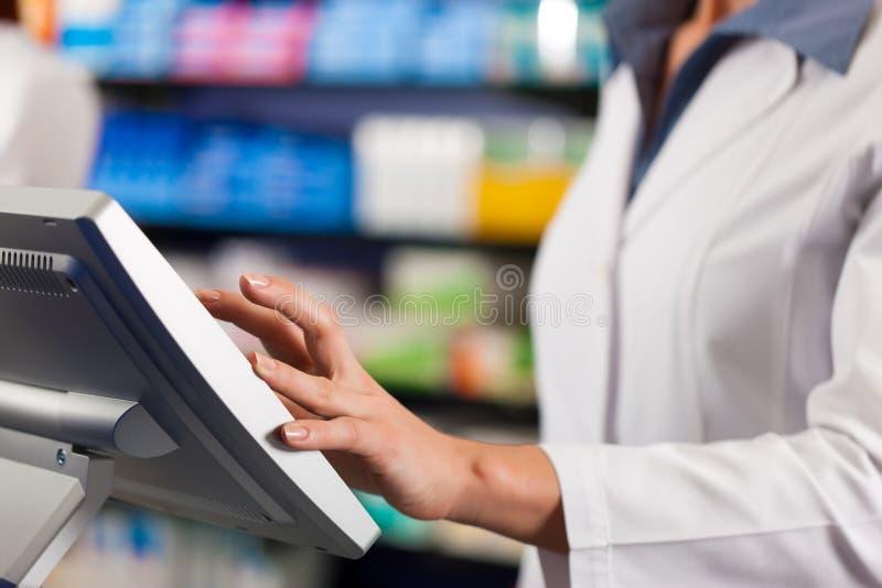Farmacéutico de sexo femenino en el cajero en farmacia imágenes de archivo libres de regalías