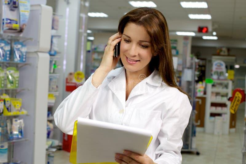Farmacéutico de sexo femenino feliz que sonríe en el teléfono fotos de archivo