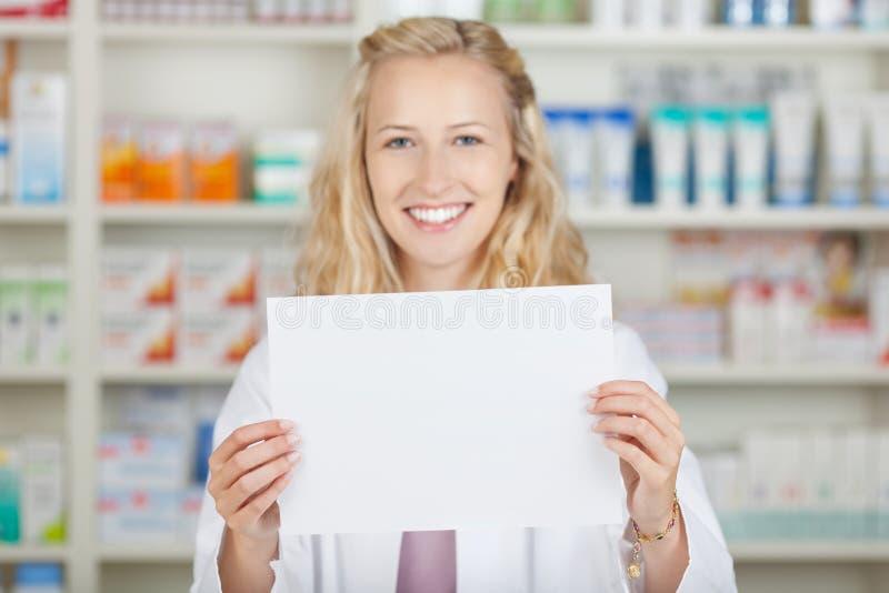 Farmacéutico de sexo femenino Holding Blank Paper imagen de archivo