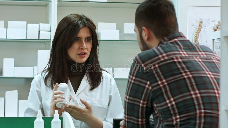 Farmacéutico de sexo femenino joven que sugiere la droga médica al comprador masculino en droguería de la farmacia fotos de archivo libres de regalías