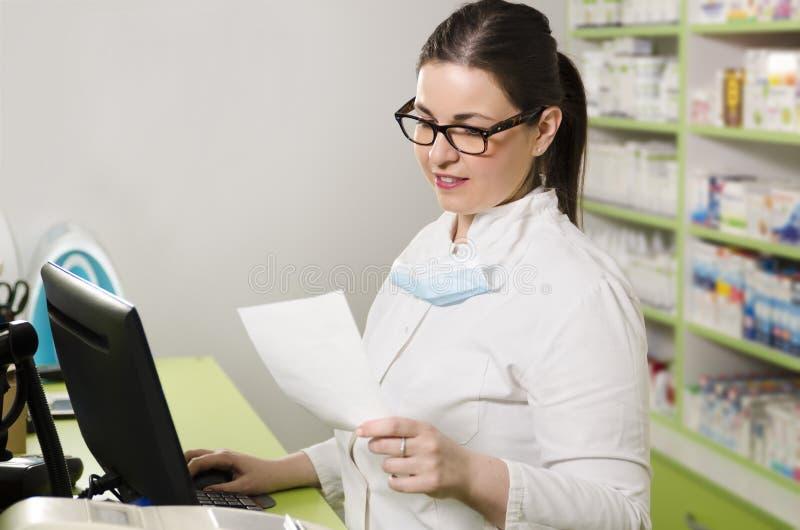 Farmacéutico de sexo femenino joven que trabaja en el ordenador imagen de archivo libre de regalías
