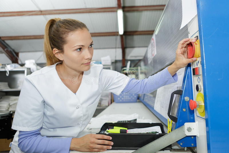 Farmacéutico de sexo femenino joven que usa la máquina en el laboratorio imagenes de archivo