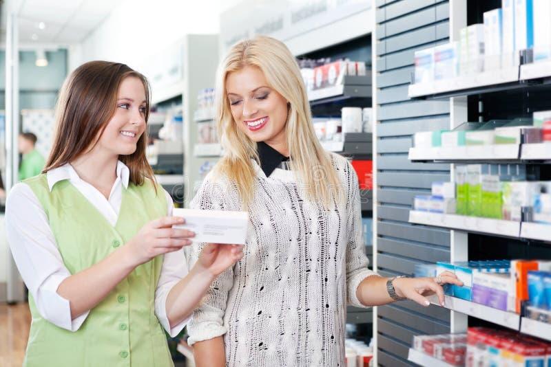 Farmacéutico de sexo femenino que aconseja al cliente imagenes de archivo