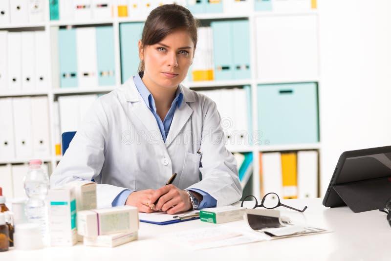 Farmacéutico de sexo femenino sentado en las notas de la escritura del escritorio fotos de archivo
