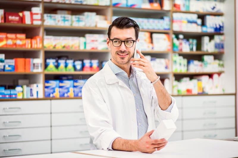 Farmacéutico de sexo masculino amistoso joven con el smartphone, haciendo una llamada de teléfono imagen de archivo libre de regalías