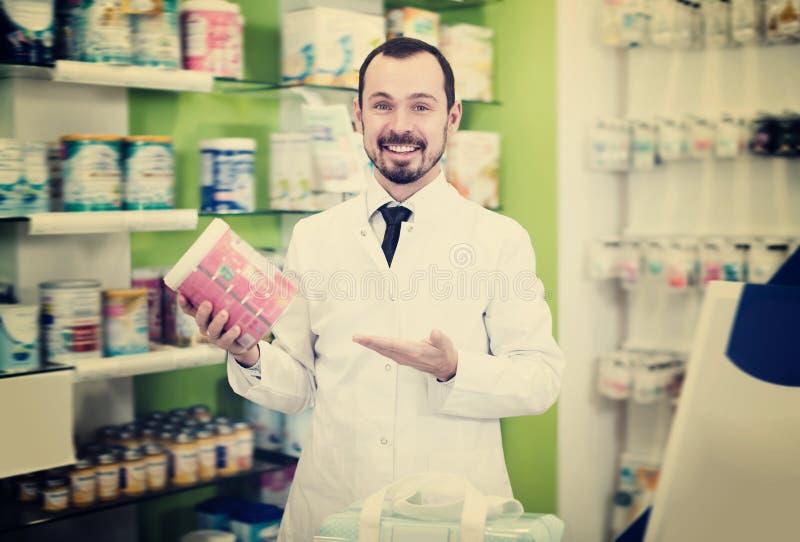 Farmacéutico de sexo masculino ordinario que sugiere la droga útil imagen de archivo