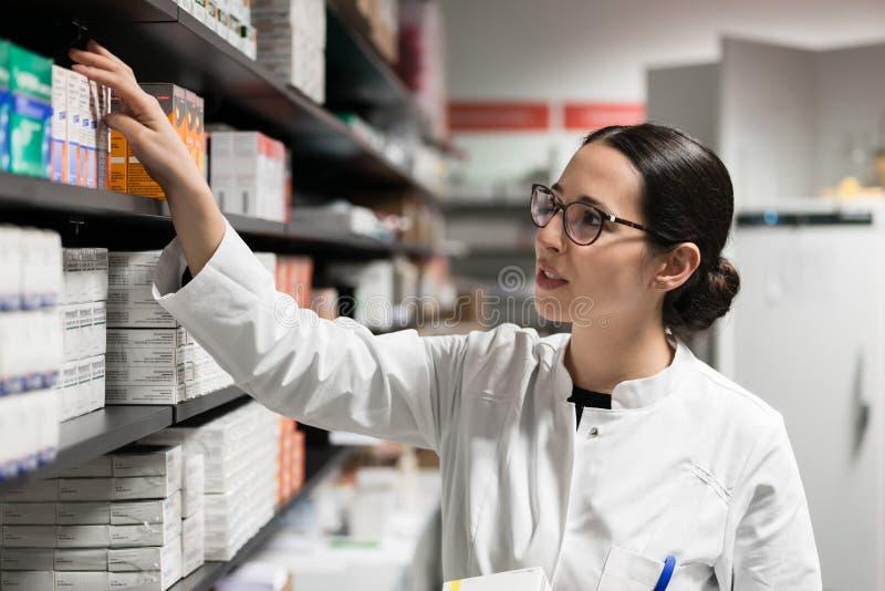 Farmacéutico dedicado que toma una medicina del estante durante trabajo foto de archivo