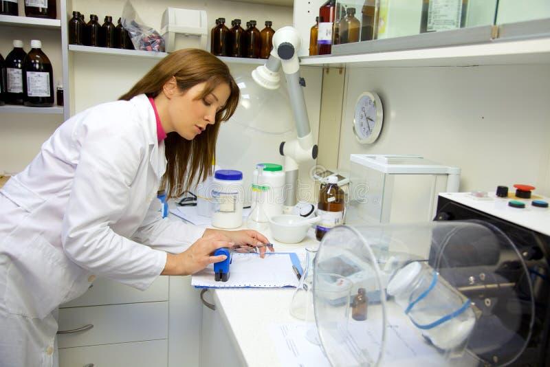Farmacéutico en el laboratorio que hace papeleo foto de archivo