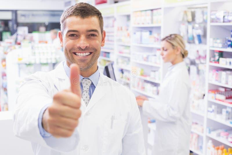 Farmacéutico feliz que se sostiene el pulgar fotografía de archivo