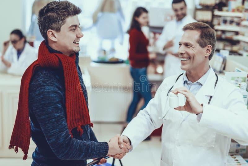 Farmacéutico Handshaking con el cliente foto de archivo