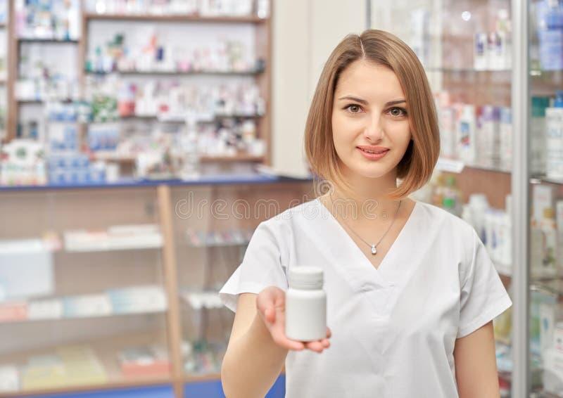 Farmacéutico hermoso de la mujer que presenta en droguería imagen de archivo libre de regalías