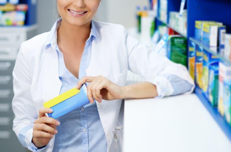 Farmacéutico hermoso de la mujer que se coloca en su lugar de trabajo en farmacia imagen de archivo libre de regalías