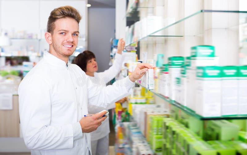 Farmacéutico hermoso del hombre que se coloca entre estantes fotos de archivo libres de regalías
