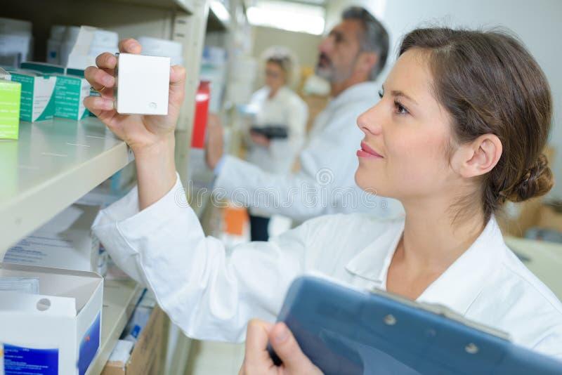 Farmacéutico joven atractivo que comprueba la acción en pasillo imagen de archivo