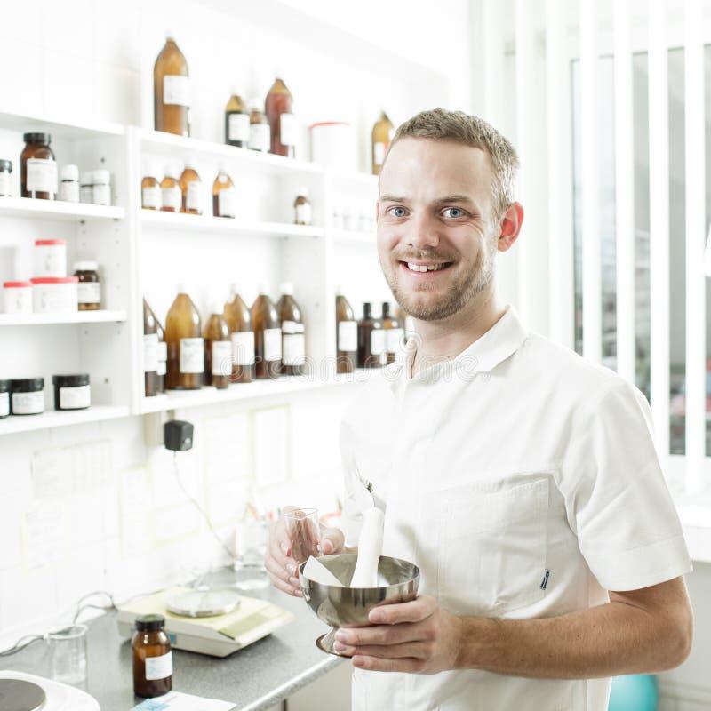 Farmacéutico joven que prepara la medicina imagenes de archivo