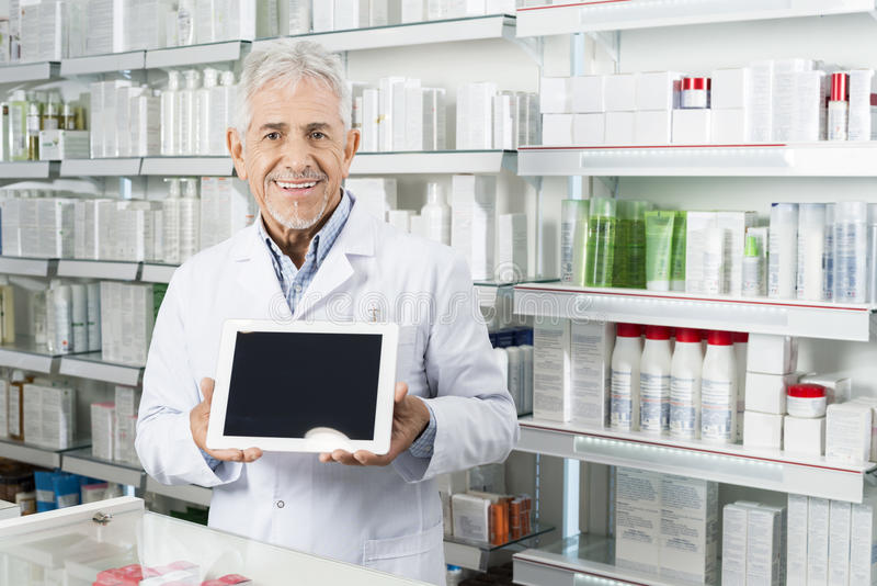 Farmacéutico mayor Holding Digital Tablet con la pantalla en blanco fotos de archivo