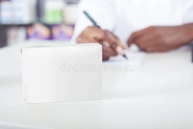 Farmacéutico o escritura del doctor con el paquete verde de la tableta con el espacio de la copia imágenes de archivo libres de regalías