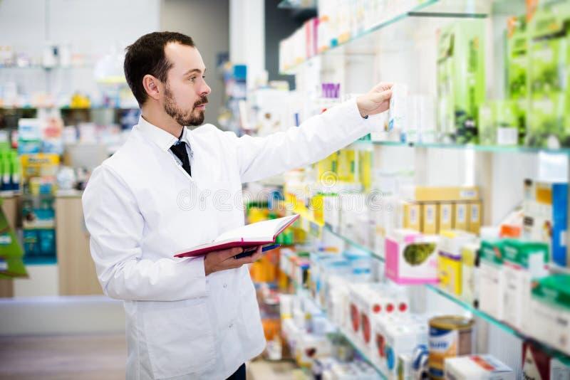 Farmacéutico que anota el surtido de drogas imagen de archivo libre de regalías