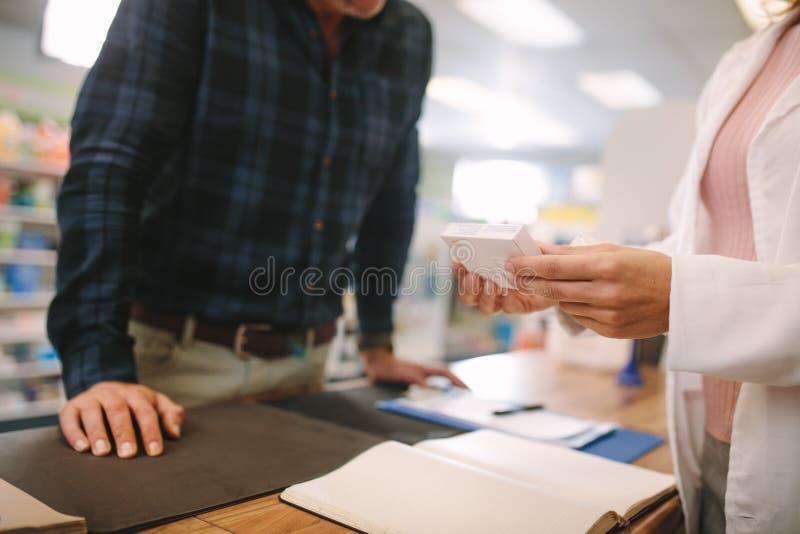 Farmacéutico que ayuda a la droga al cliente en farmacia imagen de archivo libre de regalías